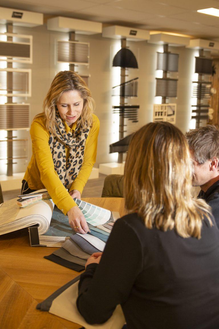 Olga Jutstra helpt klanten met het uitzoeken van behang